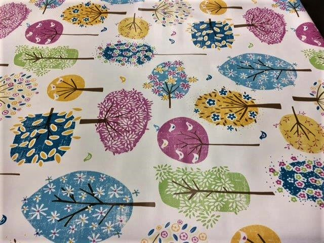 Pink, blue and gold hand painted trees on a vinyl tablecloth